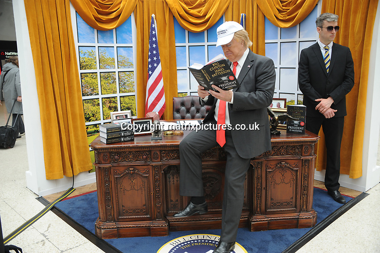 NON EXCLUSIVE PICTURE: MATRIXPICTURES.CO.UK<br /> PLEASE CREDIT ALL USES<br /> <br /> WORLD RIGHTS<br /> <br /> A President Trump impersonator poses in a mock up of the Oval office to promote the global release of James Patterson and Bill Clinton's book, The President is Missing, Waterloo Station in London.<br /> <br /> JUNE 4th 2018<br /> <br /> REF: TST 182067