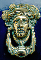 A brass door knocker in the shape of a woman's face with a laurel crown is mounted on a bright blue door. Dublin, Ireland.