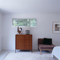 A brown chair designed by Deborah Berke stands next to a Dunbar chest of drawers beneath a narrow window in the bedroom