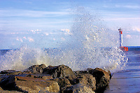 A strong wave splashes on the rocks at the base of the lighthouse pier in Oakville, Ontario