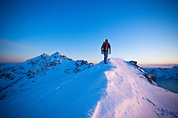 Person hikes along snow covered ridge of Stamsundheia with Steinstind peak in distance, Stamsund, Vestvågøy, Lofoten islands, Norway