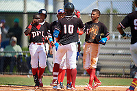 Maximo Maria (10) high fives teammates, including Daniel Gomez (3), Joseph Diaz (5) and Josefralin Alcantara (6), after hitting a home run during the Dominican Prospect League Elite Florida Event at Pompano Beach Baseball Park on October 15, 2019 in Pompano beach, Florida.  (Mike Janes/Four Seam Images)
