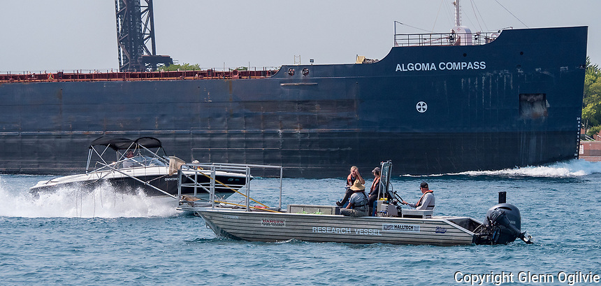 A Halltech research vessel makes its way down river while passing a cabin cruiser and the Algoma Compass