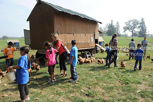 Children feed chickens at the chicken coop as United States First Lady Michelle Obama visits Stone Barns Center in Pocantico Hills, New York on Friday, September 24, 2010 with a large group of other First Ladies visiting New York for the United Nations General Assembly. They viewed the mobile chicken coop and herb garden while making a tour of the facilities.  .Credit: Andrea Renault / Pool via CNP