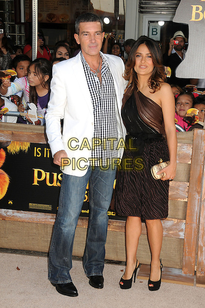 Antonio Banderas and Salma Hayek.The L.A. Premiere of 'Puss in Boots' held at The Regency Village Theatre in Westwood, California, USA..October 23rd, 2011.full length dress black brown sheer one shoulder gold clutch bag jeans denim white suit jacket check shirt .CAP/ADM/BP.©Byron Purvis/AdMedia/Capital Pictures.