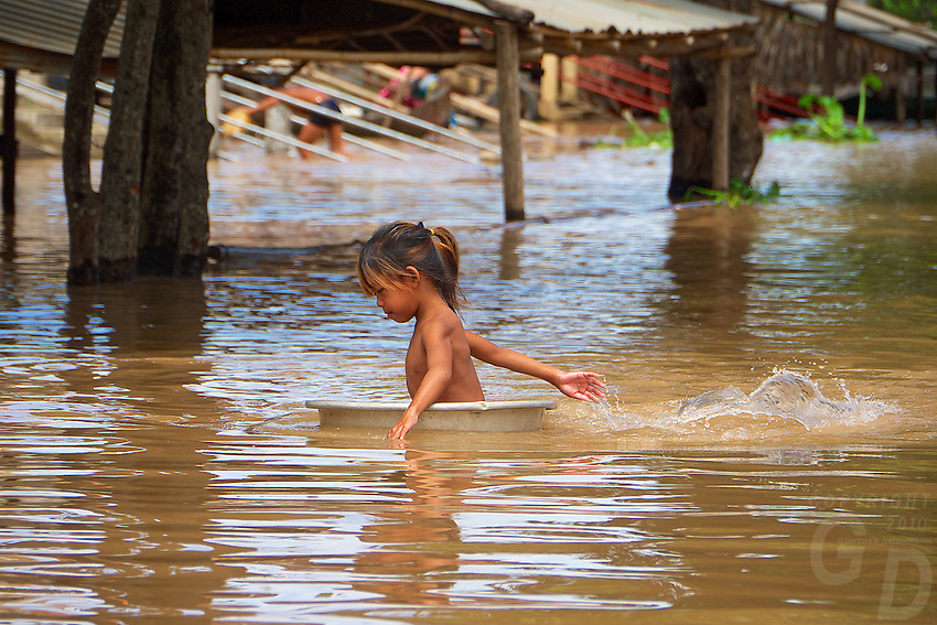 A child paddling along traveling in her washbasin or washing tub on the Tonle Sap lake, This is a way life and transportation amongst the local population especially during the Monsoon season.  Going from house to house. Cambodia
