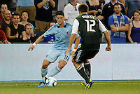 Milos Stojcev (88)  midfielder Sporting KC takes on David Horst (12)  defender Portland Timbers... Sporting Kansas City defeated Portland Timbers 3-1 at LIVESTRONG Sporting Park, Kansas City, Kansas.