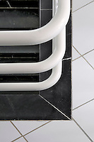 A detail of the enamelled white balustrade of the main staircase of the hotel seen against the black and white ceramic tiled floor of the landing