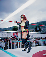 "Diabolica, a ""Luchadora"" (female wrestler) looks out  at the crowd in Ecatepec, Estado de Mexico. Diabolica is what is known as a wrestler that is ""Ruda"" (these are the badies) as opposed to ""Tecnico"" who are the ones who follow the rules (goodies). Mexico, June 2004"