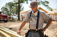 NWA Democrat-Gazette/CHARLIE KAIJO Robert Mitchell of Joplin Mos. takes a break from sawing posts for the construction of a porch on a home building project, Friday, June 8, 2018 on Passion Play Road, across the street from the Washington Regional clinic in Eureka Springs. <br /><br />Eight tiny houses are being built in Eureka Springs, which has a dearth of affordable housing. They're being constructed by 66 volunteers from 13 states with World Mission Builders. They began work on Monday (June 4) and should finish most of the construction by the end of next week (June 15). Then local volunteers will finish out the interiors and put shingles on the roofs. The first eight houses are part of what will be called ECHO Village. Plans are to eventually have 26 houses in the village. It's a project of Eureka Christian Health Outreach, which bought 10 acres for the village. The same group started ECHO Clinic in Eureka Springs in 2005. It provides free medical care to the uninsured and people on a low income.