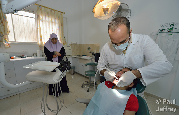 As her mother looks on, Kefah El Jadba, 9, gets her teeth worked on by a dentist in a clinic in Darraj, a neighborhood of Gaza City that was hard hit by the Israeli military during the 2014 war. The clinic is run by the Department of Service for Palestinian Refugees of the Near East Council of Churches, a member of the ACT Alliance, and funded in part by the Pontifical Mission for Palestine.