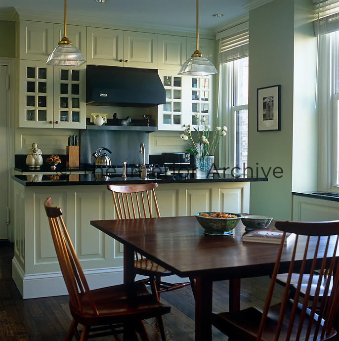 In a New York kitchen-diner the cupboards have been painted a pale shade of celadon in elegant contrast to the dark stone work surfaces