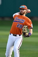 Right fielder Seth Beer (28) of the Clemson Tigers warms up in the outfield between innings of a game against the William and Mary Tribe on February 16, 2018, at Doug Kingsmore Stadium in Clemson, South Carolina. Clemson won, 5-4 in 10 innings. (Tom Priddy/Four Seam Images)