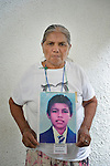 Ercilia Ayala holds a photo of her son Juan Carlos Rivera Ayala during a vigil in Tapachula, Mexico, on December 17, 2013. The Honduran woman was part of a group of Central Americans who came to Mexico in search of family members who disappeared there, many while on their way north to the United States. The group, mostly mothers looking for their children, spent 17 days touring 14 Mexican states in search of their loved ones.<br /> <br /> Ayala says her son migrated north in 2001 when he was 19 years old, and she hasn't heard from him since. The photo she carries was taken when he was 14 years old.