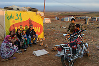 LEBANON Beqaa valley, Deir el Ahmad, camp for syrian refugees, family in tent made of MAGGI advertisement poster / LIBANON Bekaa Tal, Deir el Ahmad, Camp fuer syrische Fluechtlinge am Dorfrand
