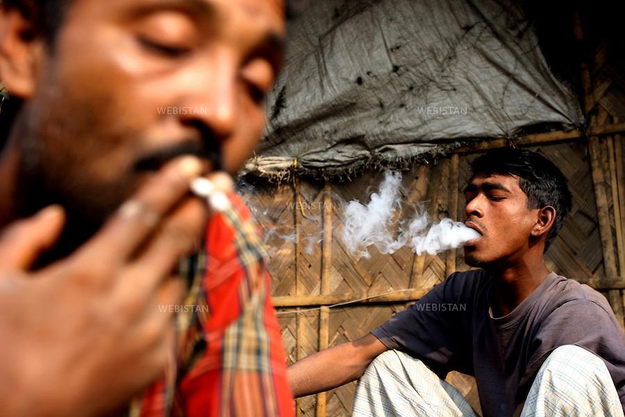 2006. Bangladesh, Dhaka. Marijuana users in a slum. .Marijuana is still the most popular addictive substance in widespread use in Bangladesh but the marijuana smoked today is said to be 15 times more potent than that smoked in the 60s. The result is that those who smoke it have significantly more respiratory symptoms like chronic cough and mucus production, wheezing, and acute bronchitis, than previously..2006. Bangladesh, Dhaka. Consommateurs de marijuana dans un bidonville. .La marijuana est encore la substance additive la plus populaire de grande consommation au Bangladesh, mais on dit que la marijuana fumée aujourd'hui est dix fois plus puissante que celle fumée dans les années 60. Par conséquent ceux qui la fument ont beaucoup plus de troubles respiratoire comme par exemple des toux chroniques et production de mucus, des poumons sifflant et des bronchites aigues qu'avant..