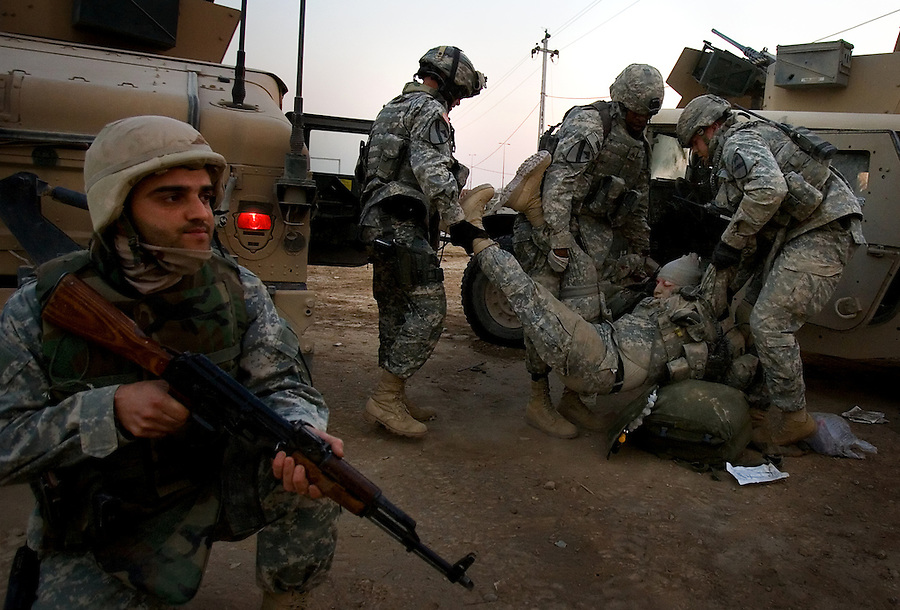 Three soldiers attached to an Military Transition Team (MiTT) - US advisors attached to the Iraqi Army - pull a wounded comrade hobble away from a damaged Humvee following an IED strike as they work to load him into a second Humvee for evacuation in the Diyala provincial capital, Baqubah on Mon. Dec. 4, 2006. The soldier - part of the 1st Cavalry Division - succumbed to his wounds later that evening.<br />