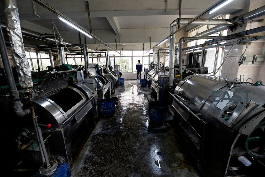 A worker in the blue jeans washing room of Congshin textile factory in Xintang, Guangdong province, China, on February 9, 2012. Photo by Lucas Schifres/Pictobank