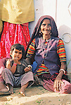 An elderly woman cradles a young child with her leg in a remote village in Gujarat.