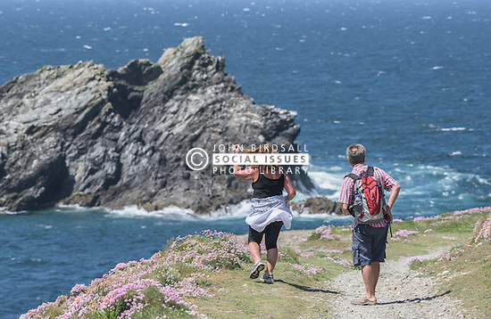 Holidaymakers walking on East Pentire Headland in Newquay, Cornwall.