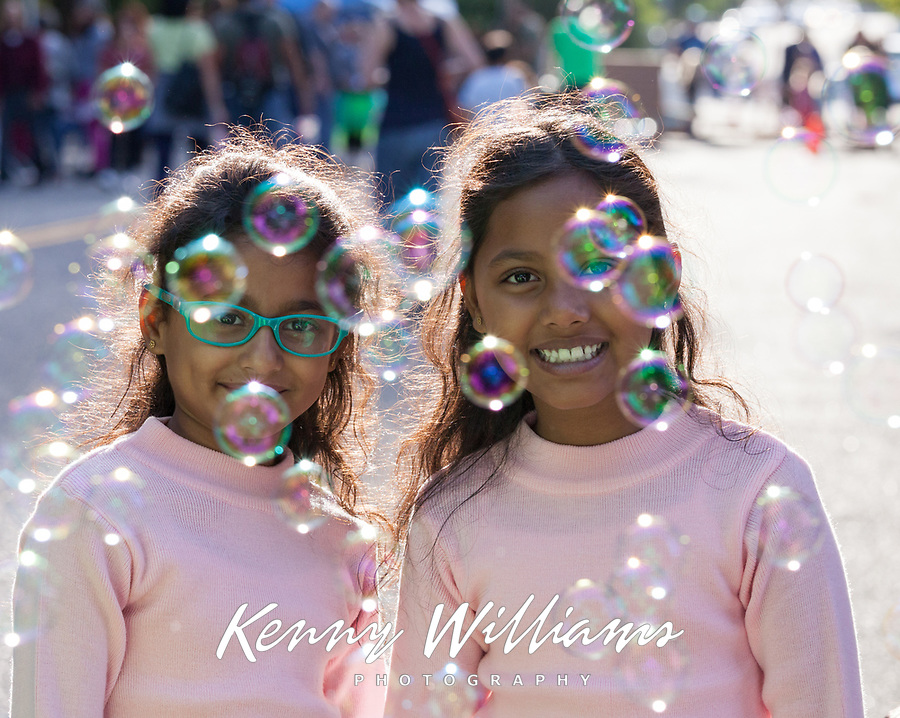 Two cute Indian girls surrounded by bubbles, Arts A Glow Festival, Burien, WA, USA.