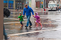 New York, NY -  29 Oct 2012 A father with two small children rush across East 8th Street, in the East Village, during Hurricane Sandy