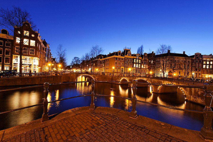 Illuminated canal bridges at night, Amsterdam, Netherlands