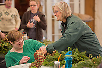 Friends of the Wissahickon Trail Ambassador Susan Simon helps Maureen B. McElroy decorate her wreath at the Winter in the Wissahickon event hosted by the Friends of the Wissahickon on December 1. (Dave Tavani/for NewsWorks)