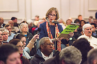 "Diane Turco, of Harwick, Mass., speaks at a public hearing regarding Pilgrim Station, a nuclear power plant run by Entergy, at Hotel 1620 in Plymouth, Massachusetts, USA, on Tues., Jan. 31, 2017. Turco is the director of the Cape Downwinders, a group of area residents opposing the continued operation of Pilgrim Station. Truco was the recipient of an email from the NRC that was leaked in December 2016 outlining problems with the ""safety culture"" at the plant and an ""overwhelmed"" staff. Area residents have been calling for the plant to be shut down. The green signs in the audience, reading ""Shut Pilgrim Now,"" are from a group of area residents calling for the plant's closure called Cape Downwinders."