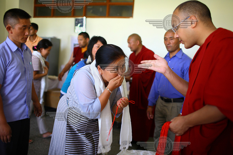 The Seventeenth Karmapa, Ogyen Drodul Trinley Dorje, greets a woman at the Gyuto Tantric Monastic University, Dharamsala. In 1992 a 7-year-old Tibetan nomad, Apo Gaga, was recognised as the Seventeenth Karmapa and went to live in Tolung Tsurphu Monastery, the historic seat of the Karmapas. He escaped Tibet for India at the turn of the millennium in order to continue without interference the primary role of the Karmapa, preserving and propagating the Buddhist teachings of Tibet.