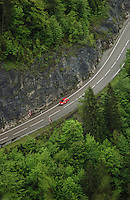 Car on alpine road with forests on both sides. Reutte district, Tyrol, Tirol, Austria.