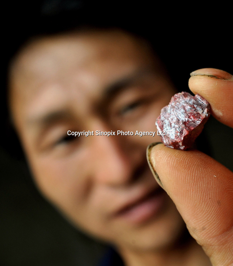 Mr Yang, manager from the Yun Chang Ping mercury mine holds a piece of mercury mined from deep with-in the mountains about 30 kilometers from Tongren city, Guizhou, China. .
