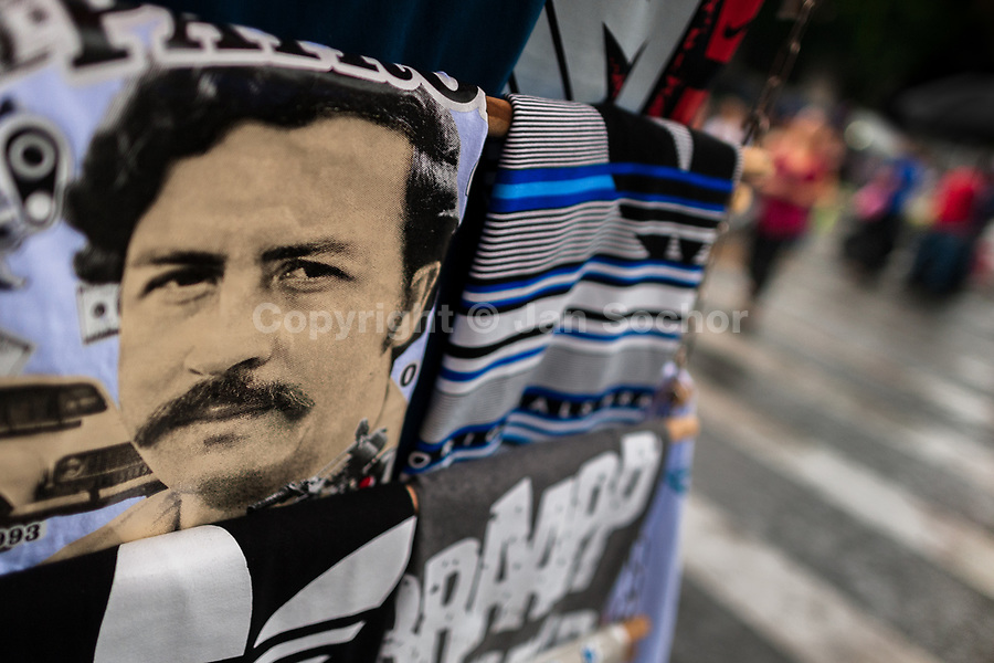 """A t-shirt for sale, depicting the drug lord Pablo Escobar, is seen arranged at the market stand on the street in Medellín, Colombia, 1 December 2017. Twenty five years after Pablo Escobar's death, the legacy of the Medellín Cartel leader is alive and flourishing. Although many Colombians who lived through the decades of drug wars, assassinations, kidnappings, reject Pablo Escobar's cult and his celebrity status, there is a significant number of Colombians who admire him, worshipping the questionable """"Robin Hood"""" image he had. Moreover, in the recent years, the popular """"Narcos"""" TV series has inspired thousands of tourists to visit Medellín, creating a booming business for many but causing a controversial rise of narco-tourism."""