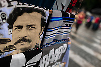 "A t-shirt for sale, depicting the drug lord Pablo Escobar, is seen arranged at the market stand on the street in Medellín, Colombia, 1 December 2017. Twenty five years after Pablo Escobar's death, the legacy of the Medellín Cartel leader is alive and flourishing. Although many Colombians who lived through the decades of drug wars, assassinations, kidnappings, reject Pablo Escobar's cult and his celebrity status, there is a significant number of Colombians who admire him, worshipping the questionable ""Robin Hood"" image he had. Moreover, in the recent years, the popular ""Narcos"" TV series has inspired thousands of tourists to visit Medellín, creating a booming business for many but causing a controversial rise of narco-tourism."