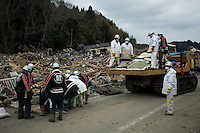 Rescue workers lift bodies onto the back of a truck. Thousands of people died in this small town which ran out of body bags. On 11 March 2011 a magnitude 9 earthquake struck 130 km off the coast of Northern Japan causing a massive Tsunami that swept across the coast of Northern Honshu. The earthquake and tsunami caused extensive damage and loss of life.