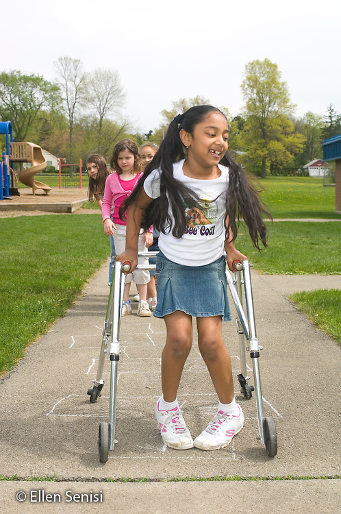MR / Schenectady, NY.Zoller school (urban public school) / grade 2 Inclusion class.Girl (7, cerebral palsy, in walker) plays hopscotch with her friends on the playground..MR: AG-gss, Cha9.© Ellen B. Senisi