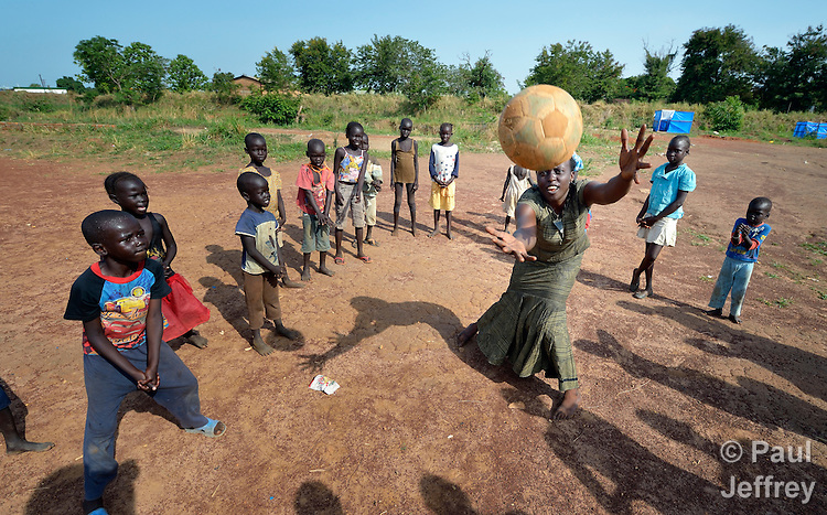 Children practice volleyball skills inside a camp for internally displaced families in Yei, South Sudan. The camp holds Nuer families who took refuge there in December 2013 after a political dispute within the country's ruling party quickly fractured the young nation along ethnic and tribal lines. The ACT Alliance is providing psycho-social services in the camp, including safe places for children to enjoy being children. Chasing the ball is Victoria Amude, program manager of children's protective services for the Institute for the Promotion of Civil Society, whose work in the camp is funded by ICCO, a member of the ACT Alliance.