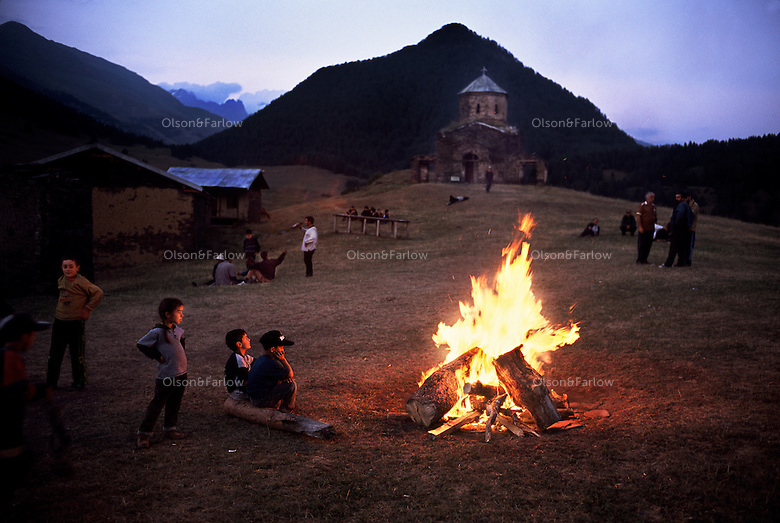 Bonfire in Tusheti. At the end of the festival day, elders build a bonfire. The church at the top of this photo has been abandoned for centuries, a relic of the world trying to change their pagan lifestyle. The ethnic group here is made up of the Khevsurs, and each village has only one family name.