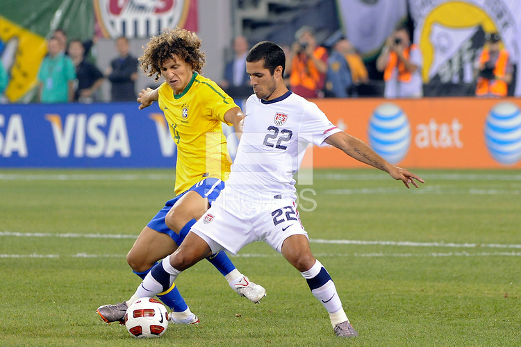 David Luiz (4) of Brazil and Benny Feilhaber (22) of the United States battle for the ball. The men's national team of Brazil (BRA) defeated the United States (USA) 2-0 during an international friendly at the New Meadowlands Stadium in East Rutherford, NJ, on August 10, 2010.