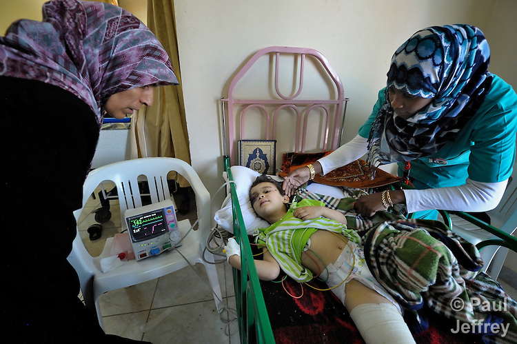 Khieria Abdulsalam (left) comforts her daughter, three-year old Aya Ali, in the Hekma Hospital in Misrata, Libya, as nurse Fozya Al-Bike accompanies the two. The girl was seriously injured on June 12 when a wall, weakened by combat in her neighborhood between rebels and troops loyal to Libyan strongman Moammar Gadhafi, fell on top of her. She suffered a concussion, broken pelvis, broken leg, and other injuries. On her bed is a Koran. Fighting has raged in or near Misrata for months.