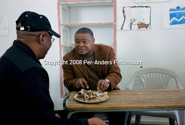 GRAHAMSTOWN, SOUTH AFRICA - JUNE 28: Zaki Makozoma (r), a businessman, chats to a friend while he eats on June 28, 2008, at the yearly arts festival in Grahamstown, South Africa. Mr. Macozoma, was sent to prison for 18 years for participating in terrorist activities during the struggle years. He was later freed and became the spokesperson for the ANC, and later became a multimillionaire, with interests primarily in the banking sector. Mr. Macozoma feels best when he visits Eastern Cape, the rural areas where he grew up. A traditional man, he likes to speak to the grass root people in these areas and he often visits local restaurants to eat a traditional meal such as sheep head and sheep feet. (Photo by: Per-Anders Pettersson/Getty Images).