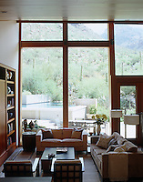 The windows in the spacious living room overlook the terrace and pool which were carved into the hillside