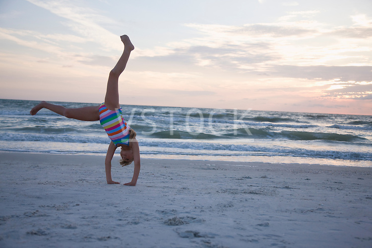 USA, Florida, St. Pete Beach, girl (8-9) cartwheeling on beach