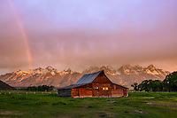Moulton Barn at sunrise with rainbow on Mormon Row against the Teton Range Mountains in Grand Teton National Park.