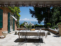 An outdoor dining area on a stone-flagged terrace in the garden has views over Lake Geneva
