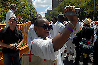 "A congregant videotapes the mass baptism of the United House of Prayer for All People, a non-denominational Pentecostal church in Harlem in New York on Sunday, August 3, 2008. The church, which has held the baptisms on West 115 street since 1937, uses a fire hose to spray the congregation with city water blessed by the church's bishop. The ceremony is accompanied by music played by several brass ""shout"" bands. (© Richard B. Levine)"