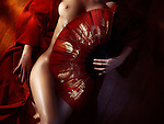 Beautiful naked woman body in red kimono covered with an oriental fan, fine art nude zen artistic concept
