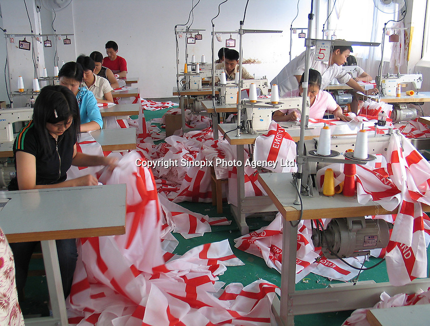 Worker sew English flags at Zhejiang Dyeing and Weaving co. Ltd. in Shaoxing, China. The factory which is exporting thousands of flags is flat out to meet demand for the Euro 2004 soccer tournament and is turning away orders..11-JUN-04