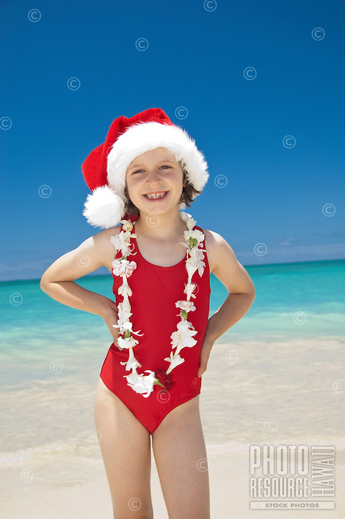 Young girl in santa hat and red swimsuit on beach with flower lei