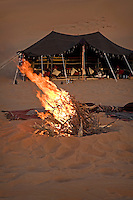 Throws and cushions are arranged around the camp fire lit to ward off the cold of the desert night